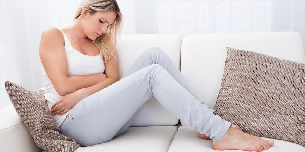 kobieta cierpiąca na PMS trzyma się za brzuch