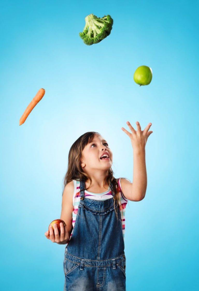Zadowolone dziecko żonglujące warzywami.