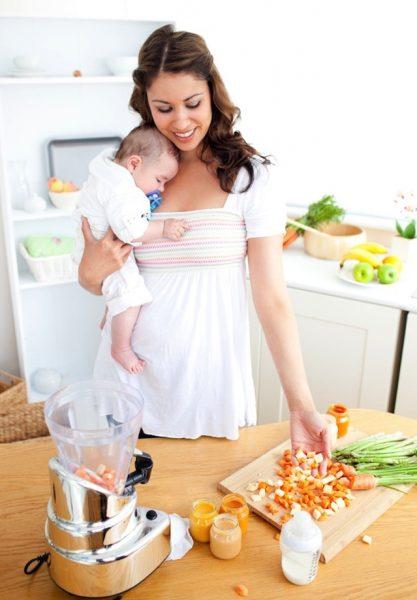szczesliwa kobieta trzymająca dziecko rękach przygotowujaca zdrowy domowy posilek