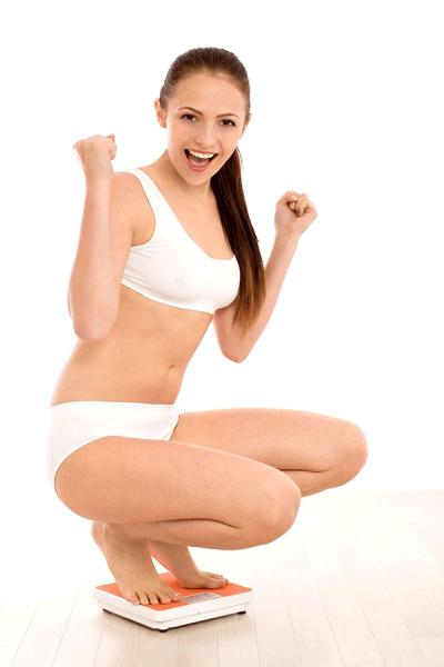 usmiechnieta kobieta stojaca na wadze z zaciesnietymi piesciami bo udalo sie schudnac